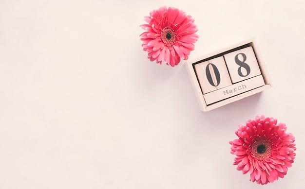 Inscripción del 8 de marzo en bloques de madera con flores.