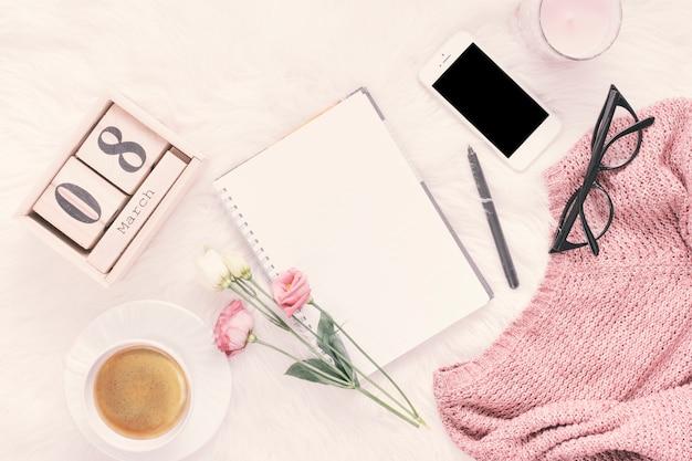 Inscripción del 8 de marzo con cuaderno, rosas y teléfono inteligente.