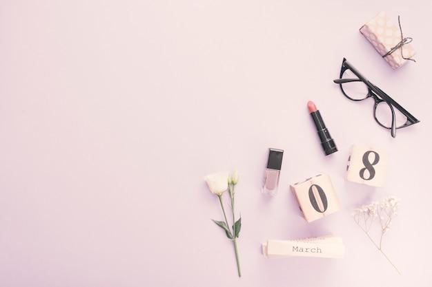 Inscripción del 8 de marzo con flores y cosméticos en mesa.