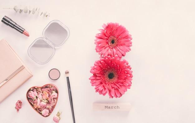 Inscripción del 8 de marzo de flores de gerbera con cosméticos en mesa.