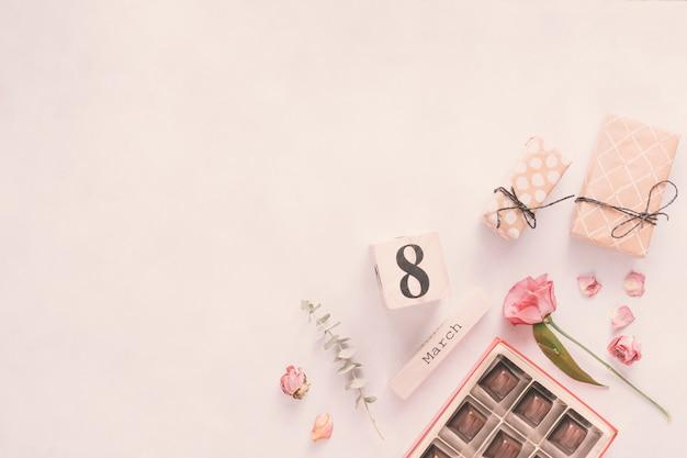 Inscripción del 8 de marzo con flores, regalos y dulces de chocolate.