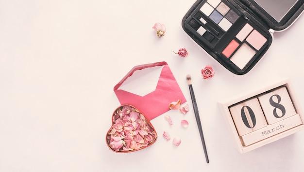 Inscripción del 8 de marzo con pétalos de rosa, sobre y sombras de ojos.
