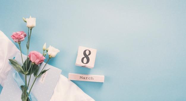 Inscripción del 8 de marzo con rosas en mesa.