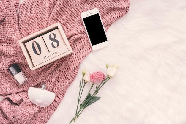 Inscripción del 8 de marzo con smartphone y rosas sobre manta.
