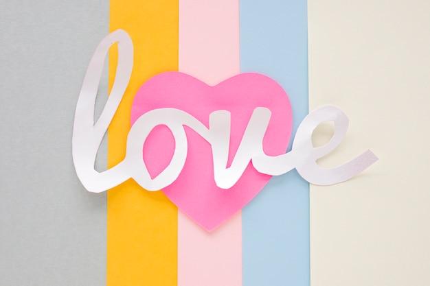 Inscripción de amor blanco con corazón rosa en mesa brillante