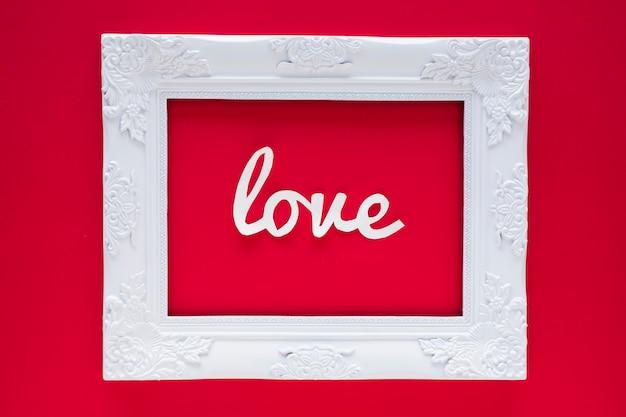 Inscripción de amor blanco en marco sobre mesa roja