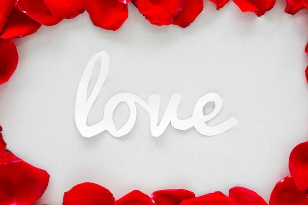 Inscripción de amor de papel con pétalos de rosa en mesa de luz.