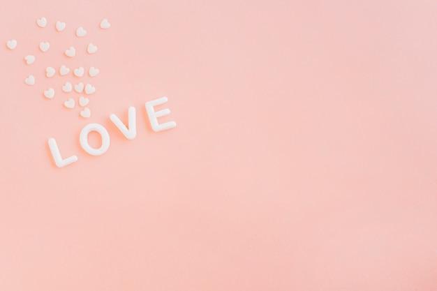 Inscripción de amor con pequeños corazones en mesa.