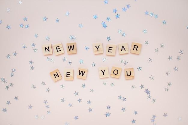 La inscripción año nuevo nuevo a partir de bloques de madera con estrellas plateadas.