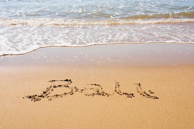 Inscripción de bali en una playa de arena tropical con olas y espuma