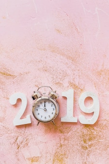 Inscripción blanca 2019 con reloj en mesa rosa.