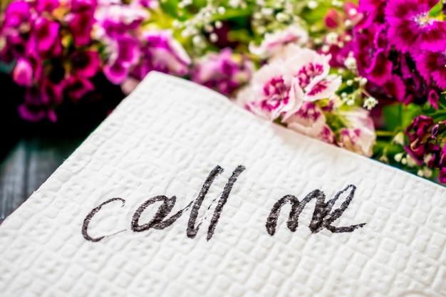 La inscripción call me sobre una servilleta blanca.