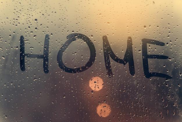 La inscripción a casa en el cristal sudoroso.