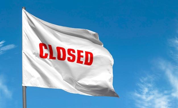 Inscripción cerrada con letras rojas en bandera blanca contra el cielo azul.
