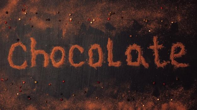 Inscripción de chocolate hecha de cacao en polvo con la adición de trozos de chocolate