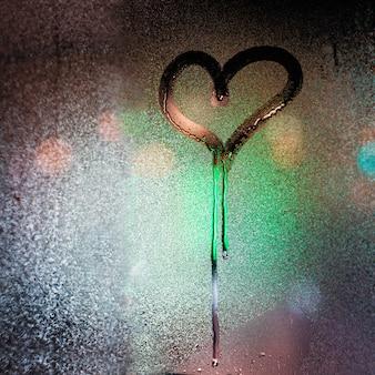 Inscripción de corazón y amor en el vidrio empañado contra