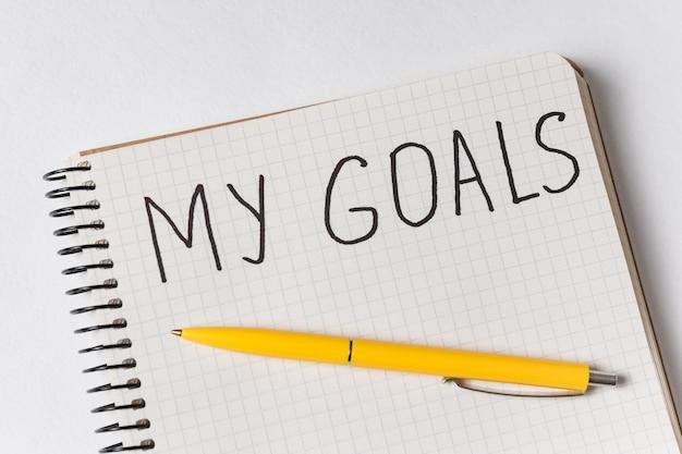 Inscripción en cuaderno mis metas. bolígrafo y cuaderno. de cerca.