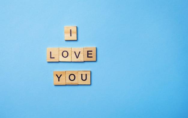 La inscripción en cubos de madera te amo, colocada en una pared azul, vista superior.