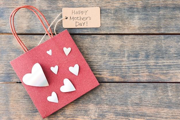Inscripción del día de la madre feliz con bolsa de papel y corazones
