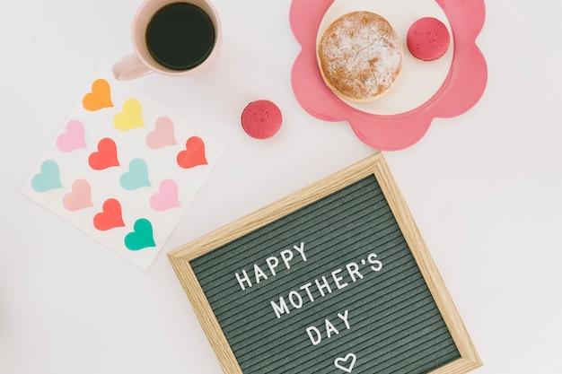 Inscripción del día de la madre feliz con café y dulces.