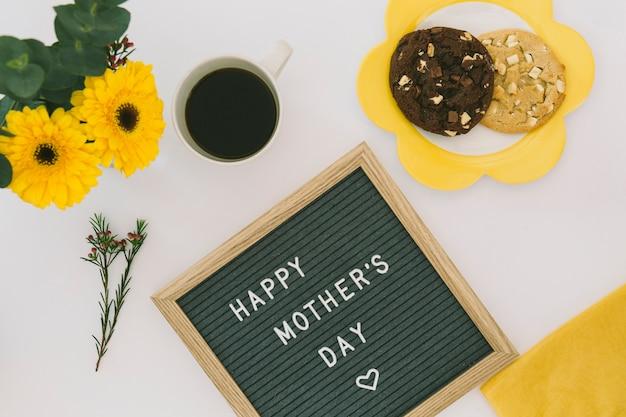 Inscripción del día de la madre feliz con café y galletas
