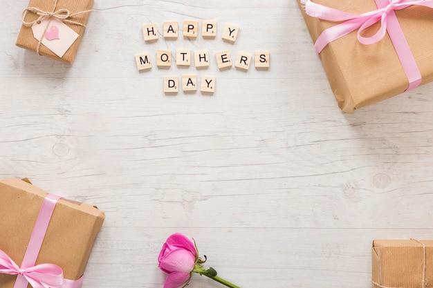 Inscripción del día de la madre feliz con caja de regalo y rosa