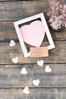 Inscripción del día de la madre feliz con flores, corazones de papel y marco