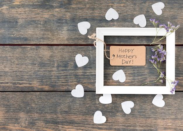 Inscripción del día de la madre feliz con flores y corazones pequeños