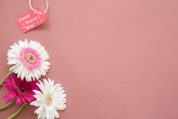 Inscripción del día de la madre feliz con flores de gerbera