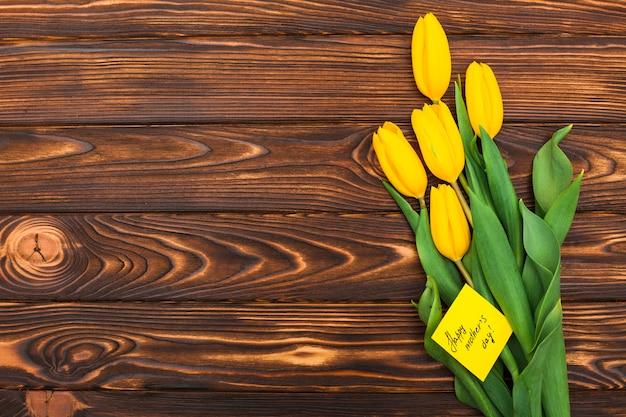 Inscripción del día de la madre feliz con flores de tulipán