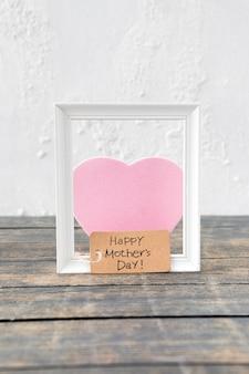 Inscripción del día de la madre feliz con marco y corazón rosa