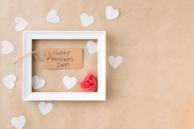 Inscripción del día de la madre feliz con marco y corazones de papel