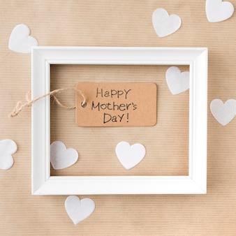 Inscripción del día de la madre feliz con marco y corazones