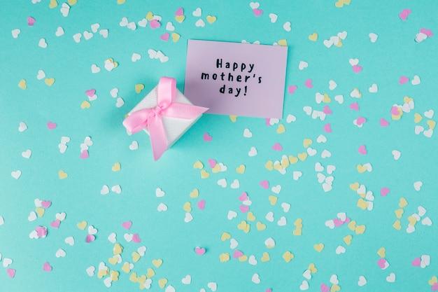 Inscripción del día de la madre feliz con una pequeña caja de regalo.