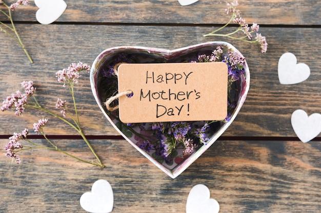 Inscripción del día de la madre feliz con pequeñas flores en caja