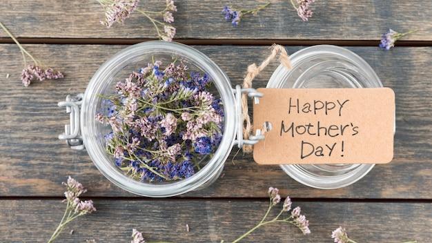 Inscripción del día de la madre feliz con pequeñas flores en lata