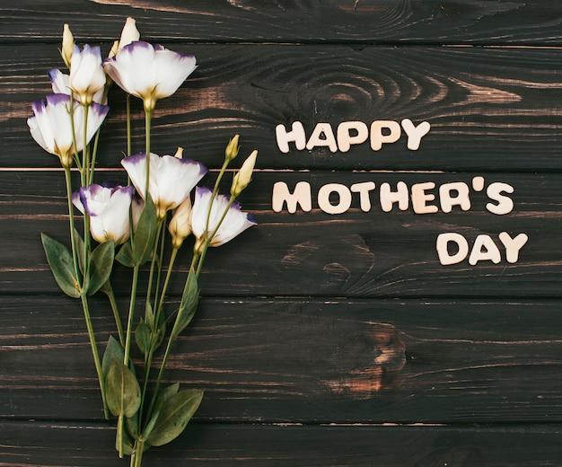 Inscripción del día de la madre feliz con ramo de flores