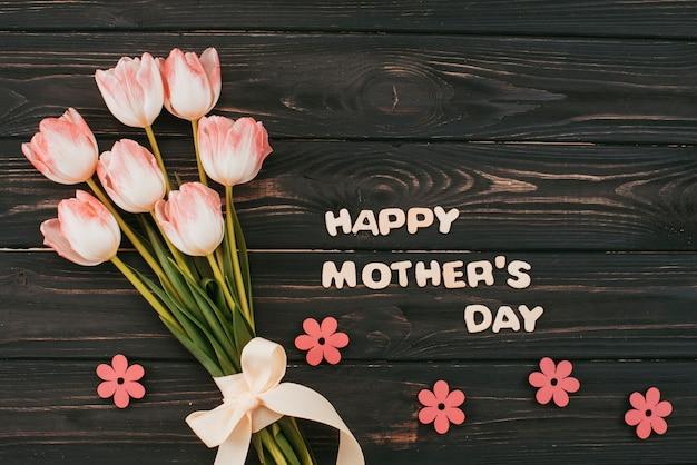 Inscripción del día de la madre feliz con ramo de tulipanes
