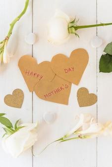 Inscripción del día de la madre feliz con rosas blancas