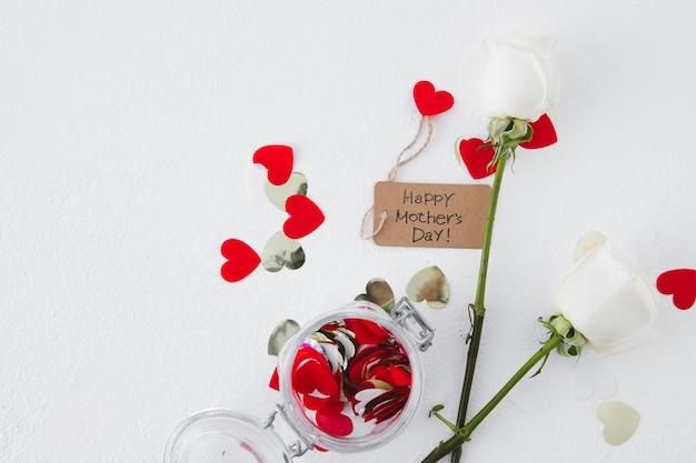 Inscripción del día de la madre feliz con rosas y corazones de papel