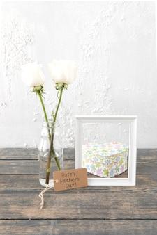 Inscripción del día de la madre feliz con rosas en jarrón y marco