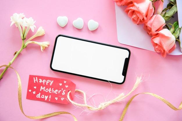 Inscripción del día de la madre feliz con teléfono inteligente y flores