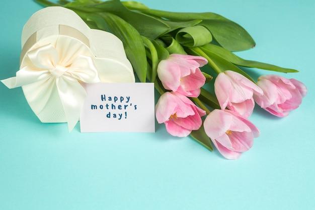 Inscripción del día de la madre feliz con tulipanes y regalo