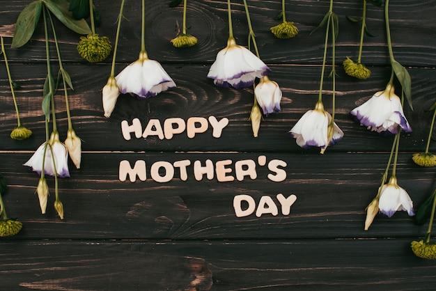 Inscripción del día de las madres felices con flores en la mesa
