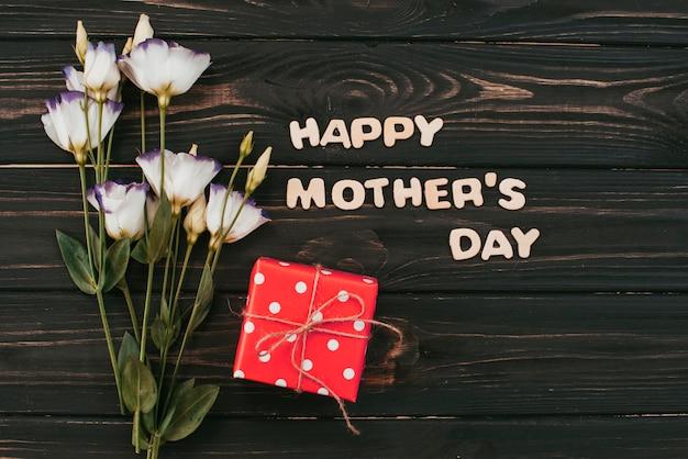 Inscripción del día de las madres felices con flores y regalos