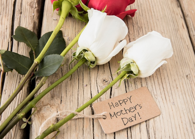 Inscripción del día de las madres felices con rosas en la mesa