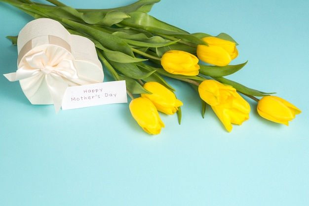 Inscripción del día de las madres felices con tulipanes amarillos y regalo