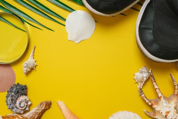 Inscripción del día mundial del turismo sobre fondo amarillo, con hojas de palmera, concha de almeja y zapatos de fondo plano