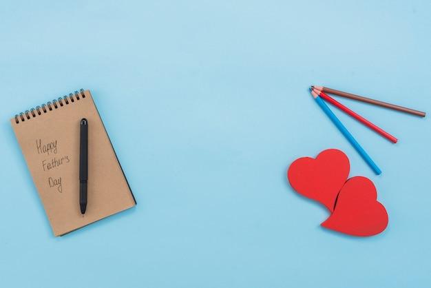 Inscripción del día de padres feliz en el bloc de notas con corazones