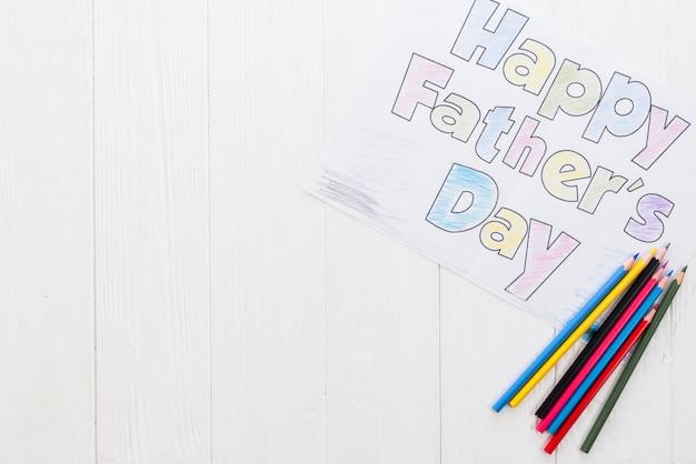 Inscripción del día de padres feliz con lápices en mesa blanca